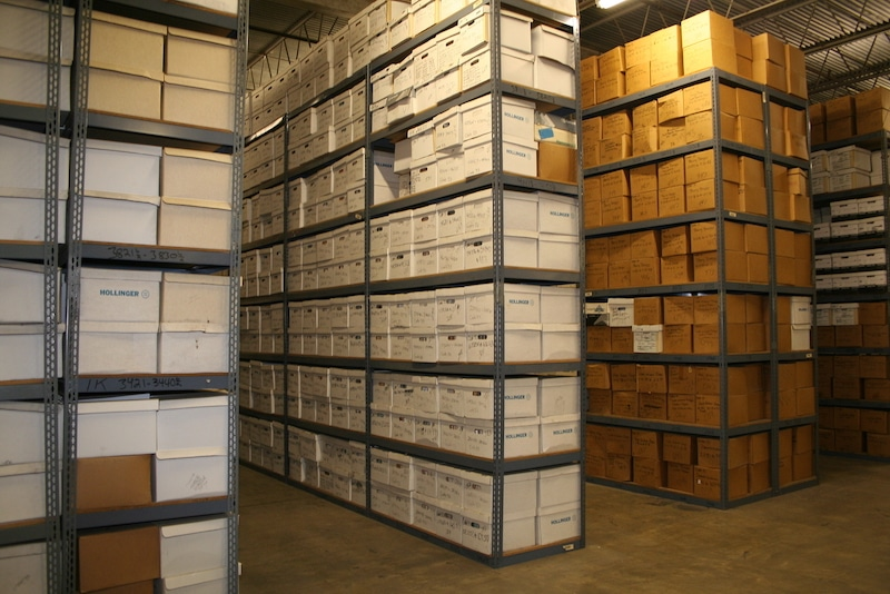a large quantity of boxes are stored on racks at this records storage warehouse facility. the boxes contain files, documents, papers, and other business records. these photos may be of special interest to those in the records management industry.